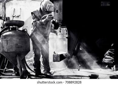 Sandblasting - industrial metal working. Black white photo