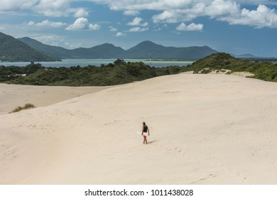 Sandboarder on sand dunes in Joaquina Beach, Florianopolis, Santa Catarina Island, South Brazil