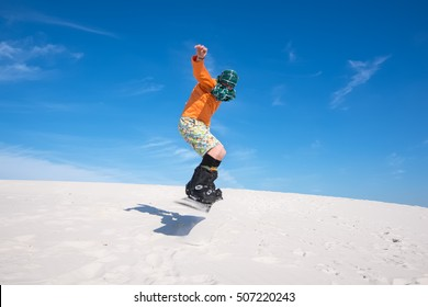 Sandboarding in desert at sunny day. Snowboarder is jumping and having fun, in preparation for the new winter season. Front view.