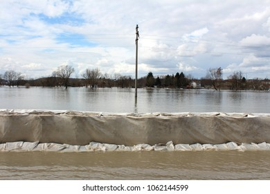 Sandbox barriers flood protection completely covered with geotextile fabric with sandbox flood protection in front and flooded river, electric pole, trees and houses in background on cloudy winter day