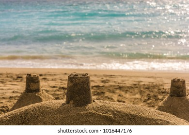 Sandcastle on a beach in the sunshine with sea in the background and open space