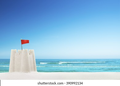 A sandcastle on a beautiful white sand beach in summer.