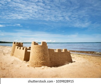 Sandcastle on the sea in summertime. Seashore on beautiful day. Sand on the beach and blue water