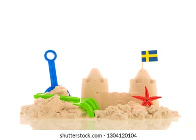 Sandcastle with plastic toys and flags isolated over white background