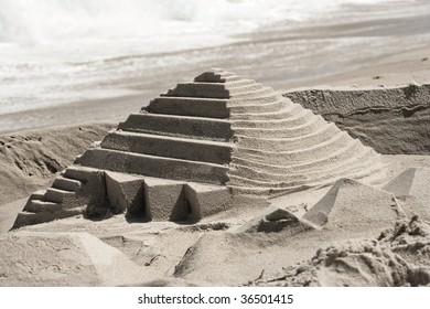 A sandcastle shaped like a pyramid on a beach