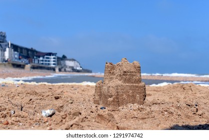 A sandcastle starts to crumble away as the incoming tide approaches in this seaside photo taken on the beach in Ramsgate