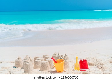 Sandcastle at white sandy beach with plastic kids toys and sea background