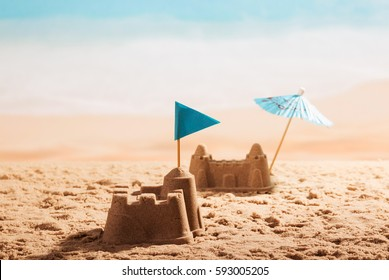 Sandcastles with a flag and an umbrella on the beach.