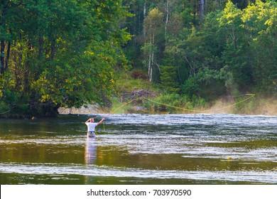 SANDE, NORWAY - 26 August, 2017: Unidentified fisherman fly fishing salmons in Gaula river near Sande town. Norway.