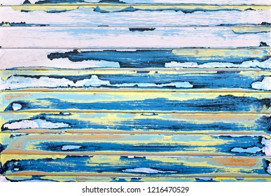 Sanded abstract paint grunge background in yellow, blue, pink and antique black on a louvered, textured wood panel