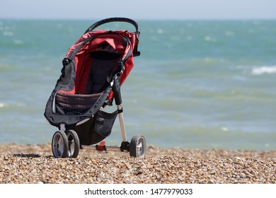 Sandgate, Kent/UK-July 22 2019: a child's pushchair stands empty on a pebble beach overlooking the English Channel