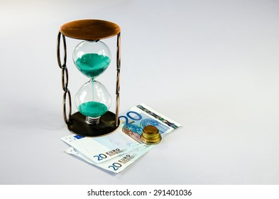 sandglass and eur banknote and coins