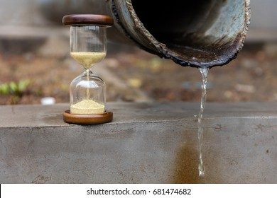 Sandglass or hourglass besides outlet with water flowing
