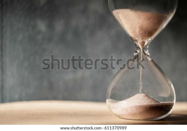 Sandglass, hourglass or egg timer on blur dark background showing the last second or last minute or time out. With copy space.