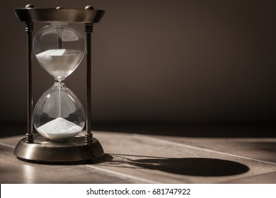 Sandglass, hourglass or egg timer with shadow showing the last second or last minute or time out. With copy space. Time management.