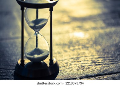 A sandglass, modern hourglass or egg timer showing the last second or last minute or time out. Cold color tone with copy space. Time is passing, deadline is approaching.