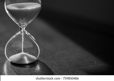 A sandglass, modern hourglass or egg timer showing the last second or last minute or time out. Black and white with copy space.