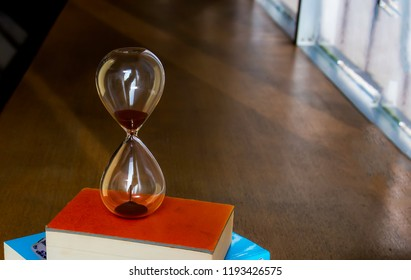 Sandglass on top of books stacked,Hourglass with books on a wooden table,Closed up of sandglass or hourglass on book using as time symbol or business deadline counting down concept.