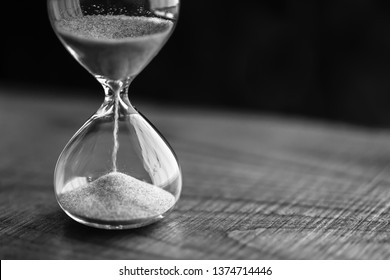 A sandglass on wooden table, modern hourglass or egg timer showing the last second or last minute or time out. Black and white with copy space.