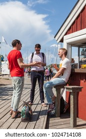 SANDHAMN, STOCKHOLM, SWEDEN, JULY 2015, three young men standing or sitting by a small red hut, talking and discussing on a beautiful summer day.
