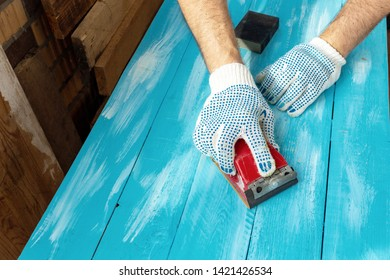Sanding blue painted wooden background hand with abrasives in a glove close up