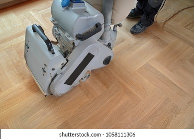 Sanding hardwood floor with the grinding machine. Repair in the apartment. Carpenter doing parquet wood floor polishing maintenance work by grinding machine