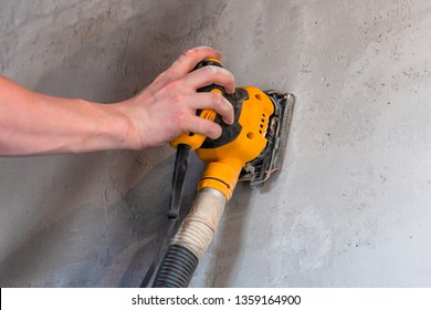 sanding a wall with a mechanical tool