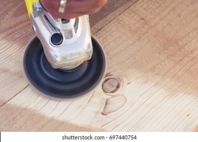 Sanding wooden sleepers  with angle grinder. Close up