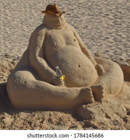 Sandman holding a bottle in the beach