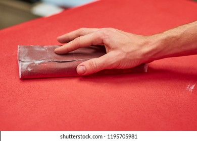 sandpaper in hand. Hands using sandpaper