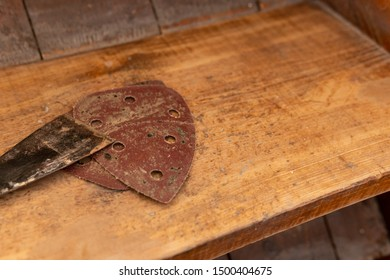 Sandpaper and putty knife lying on the wooden staircase