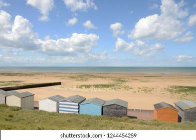 Sands and Beach huts at Minnis Bay, Kent, UK  in the Summer. This bay is used for sailing and windsurfing. Windsurfers can be seen here in the background.