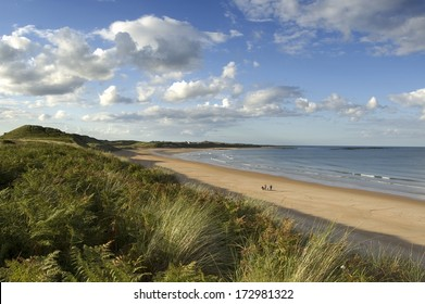 The sands of Embleton bay in late afternoon sunlight with some people walking in the distance