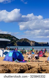 SANDSEND, NORTH YORKSHIRE, ENGLAND - AUGUST 27: Two people with their tent on the busy beach on a summer day. In Sandsend, England. On 27th August 2015.