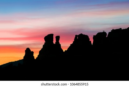Sandstone buttes near Sedona, Arizona are silhouetted by a colorful sunset sky.