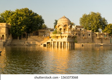 Sandstone chattri domes with steps on gadi sagar lake in jaisalmer at dusk. The golden restored runis with sunlight glinting off them birds flying around and people roaming around are tourist
