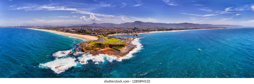 Sandstone headland with white lighthouses and breakwater stone wall protecting Wollongong harbour and marina from wild Pacific ocean waves on Australian coast in wide panorama.