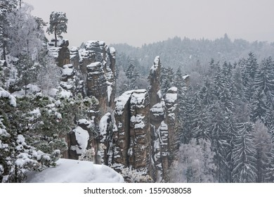 Sandstone rock area Prachovske skaly in the Czech Republic. Rocks, trees and paths are covered with snow.