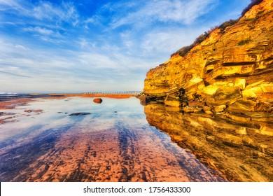Sandstone rocks of Narrabeen headland over seabed of Narrabeen beach at low tide under warm sunrise sun.
