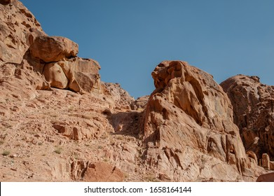 Sandstone rocks of strange forms in Sinai mountains. Stone mountain trolls. Brown rocks and blue sky. Awesome natural background. St.Catherine. South Sinai. Egypt.