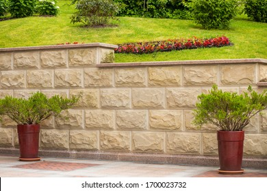 sandstone stone tile. White stone sandstone fence.  exterior of a sandstone natural stone garden. beautiful summer park with grass and natural stones. pots with landscaping.