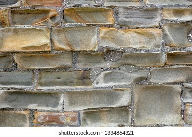 Sandstone wall that's has been weathered and eroded leaving abstract shapes and warm colours