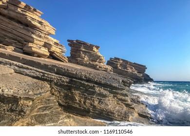 Sandstone yellow stratum rocks on coastline with crashing waves of stormy sea. Landscape.