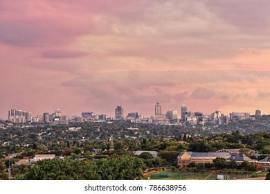 SANDTON, SOUTH AFRICA - December 24, 2017: View of the Sandton skyline including the Sandton City Shopping Mall and the Michelangelo Towers, photographed against an early evening sky.