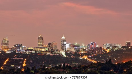 SANDTON, SOUTH AFRICA - December 24, 2017: Panoramic view of the Sandton skyline including the Sandton City Shopping Mall and the Michelangelo Towers, photographed against an early evening sky (16:9)