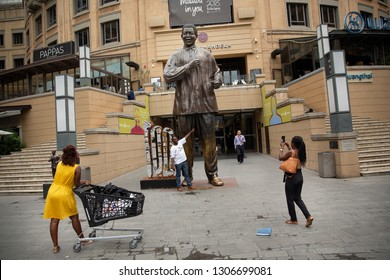 Sandton, South Africa - February 1, 2019: Take photographs with the Nelson Mandela statue at Nelson Mandela Square in Sandton City, Johannesburg