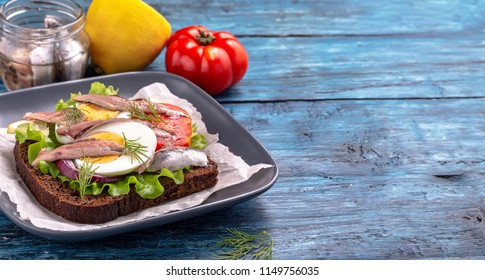 Sandwich with anchovy and egg on blue background with copy space