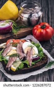 Sandwich with anchovy,egg and tomatoes on table