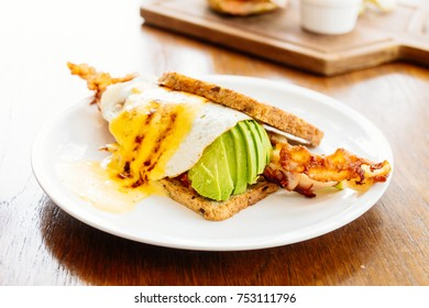 Sandwich with avocado bacon and asparagus in white plate