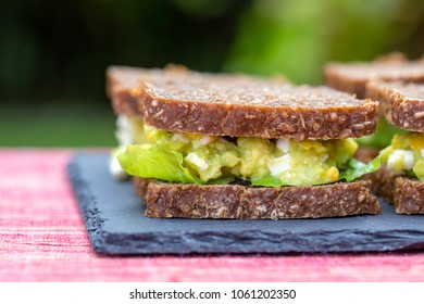 Sandwich with avocado and poached egg - healthy breakfast concept, close up